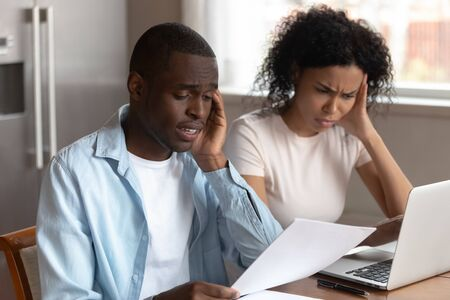 African frown couple sit at table in kitchen at home use computer online e-banking read document, overspending or debt, bankruptcy notice letter, having financial problems, check bills feels troubled