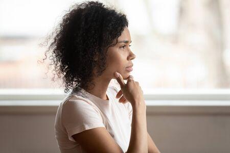 Nadenkend gemengd ras 30-er jaren vrouw die thuis zit, raakt kin aan, verloren door diepe gedachten denken maakt beslissing, zijaanzicht gezicht, uitdaging, probleemoplossing, problemen oplossen, overweging of hersenwerkconcept