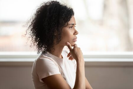 Pensive mixed race 30s woman sitting at home touch chin lost on deep thoughts thinking makes decision, side view face, challenge, problems solution, solving issues, consideration or brain work concept Standard-Bild