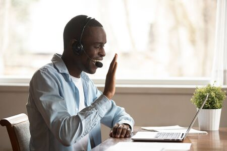 Black guy wear headset start lesson online look at laptop screen wave hand greeting tutor improves foreign language knowledge get skills through internet, education distantly using modern tech concept 版權商用圖片 - 127893975