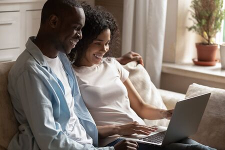 Positive african 30s couple sitting on couch using pc looking at laptop screen enjoy weekend mixed race girl black guy watching online programs videos downloaded movie, lazy activities at home concept