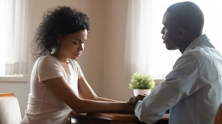 African spouses married couple sit together hold hands loving husband soothing sad wife asks for forgiveness, unfortunate pregnancy miscarriage, difficulties in life relations, health problems concept Stock Photo