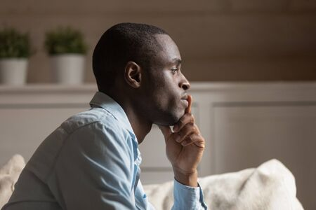 Profile face sad african guy in tension touch chin lost on thoughts thinking sit on couch in living room alone, try to make difficult decision, going through divorce or break up personal life problems Stock Photo