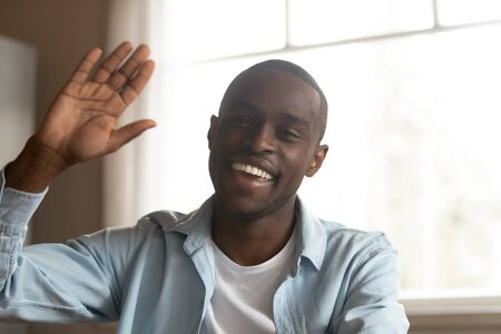 Head shot cheerful african guy look at camera wave hand greeting friend starts conversation distantly using teleconference application services, online job interview or vlogger recording vlog concept