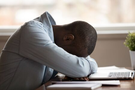 Close up view african guy sleeps on hands at table in front of pc feel drowsy, lazy student bored to study lack of energy during learning, desperate man having problems failure or debt concept image