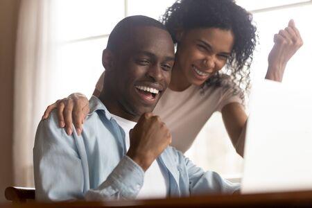 Una pareja negra de 30 años mira la pantalla de la PC se siente emocionada al celebrar los resultados de la lotería, la increíble oportunidad feliz del momento de suerte, el último pago del préstamo o la aprobación de la hipoteca, el objetivo de éxito, el concepto de gran oferta Foto de archivo