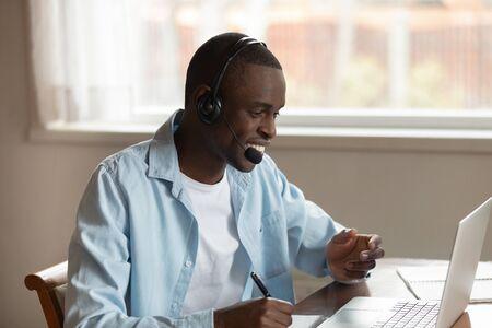Lächelnder afrikanischer Kerl trägt Headset hält Stift schreibt in Notizblock, der online lernt, Unterricht mit dem Tutor entfernt über PC zu interagieren, tausendjähriger schwarzer Mann, der das Videoseminar ansieht, das Daten notiert, fühlt sich zufrieden Standard-Bild