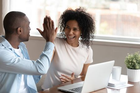 Happy african husband biracial wife couple sit at table near computer make fists yes gesture celebrating victory feels overjoyed unbelievable luck online lottery win betting, mortgage approval concept
