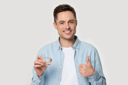 Head shot studio portrait on grey background happy young man look at camera hold glass of still water show thumbs finger up ok symbol hand gesture, healthy lifestyle, good habit, right choice concept