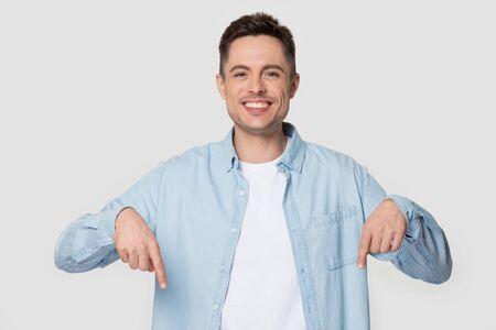 L'uomo che indossa una camicia di jeans punta le dita verso il basso guardando la telecamera sorridendo si sente bene cliente soddisfatto posa su sfondo grigio bianco studio, ragazzo pubblicizza immagine del concetto di prodotto o servizi professionali Archivio Fotografico