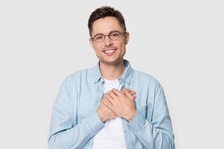 Sincere grateful young happy man wearing glasses jeans shirt smiling looking at camera pose on grey background studio shot, guy holds hands on chest show gratitude love care and honesty concept image