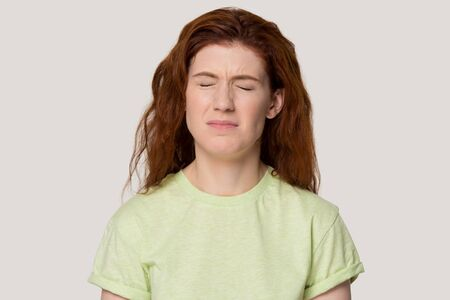 Studio head shot portrait isolated on grey background naughty capricious red-headed woman closed eyes frowning eyebrows, girl feels unhappy upset whining, always something dissatisfied person concept Stock fotó