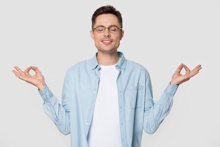 Young tranquil man in casual clothes glasses standing isolated on grey white background makes mudra gesture meditates feels internal balance having healthy habit, wellbeing harmony no stress concept Stock fotó