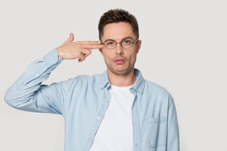 Head shot studio portrait on grey background, funny face expression man in glasses puts fingers gun gesture aimed to head killing himself symbol of exhaustion problems or unhappy depressed guy concept
