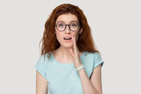 Head shot portrait on grey background red-headed girl in glasses look at camera hold hand next to mouth whispers confidential information share secret about eyewear sale better offer or gossiping news. Banque d'images - 128088713