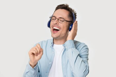 Funny millennial man wearing glasses headphones closed eyes open mouth expressively singing favourite song singer enjoy music hold hand imitate microphone like mic pose on grey white studio background. Banco de Imagens