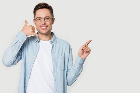 Man in glasses blue shirt smiling look at camera makes call me gesture points finger aside at announcement pose on grey white blank, copy space for advertisement text, connection communication concept