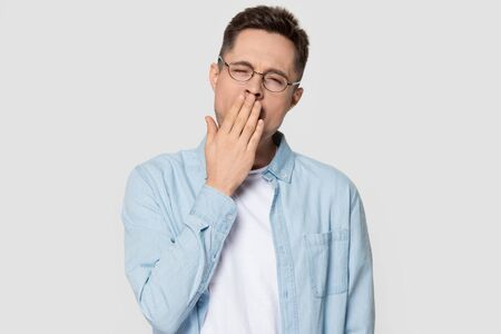 Sleepy man wearing glasses and jean shirt standing on grey white background studio shot, guy closed eyes touch cover mouth with hand yawning gaping feels lack of energy sleep or boredom concept image