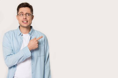 Worried nervous man in glasses points finger looking aside at empty copy space showing demonstrate something strange on freespace feels embarrassed concerned concept image isolated on grey white wall.