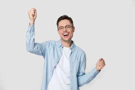 Cheerful guy raise hands celebrate win pose on grey background isolated over white wall, cheerful overjoyed guy wearing glasses jean shirt feels happy excited enjoy success victory achievement moment