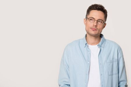 Thoughtful doubting young man standing over grey studio background looking aside at copy space for wise thought or advertisement text, serious guy in glasses considering making decision concept image
