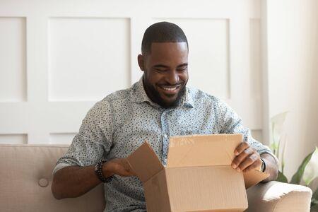 Glimlachende Afro-Amerikaanse man consument open kartonnen doos krijgt postpakket, gelukkige zwarte mannelijke klant ontvangt kartonnen pakket thuis op de bank zitten tevreden met snelle verzending online aankoop levering Stockfoto