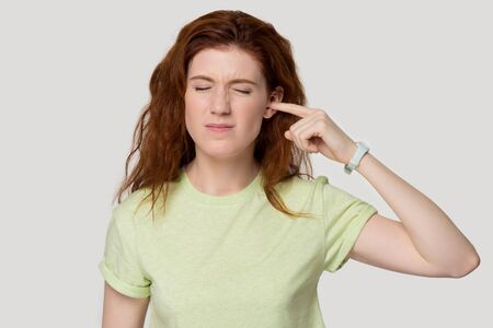 Head shot portrait grey white studio wall frowning red-headed woman closed ear with finger suffers from ear pain feels discomfort, girl in green t-shirt annoyed by loud unpleasant noise concept image