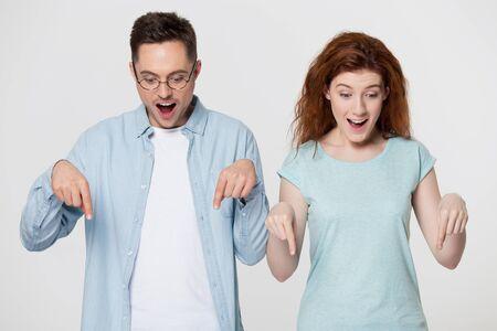 La giovane coppia si sente stupita puntare le dita guardando in basso posa su grigio, ragazza rossa con gli occhiali pubblicizza qualcosa di incredibile consiglia un nuovo negozio negozio alla moda, iscriviti al nostro concetto di gesto del canale Archivio Fotografico