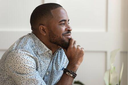 Jeune homme afro-américain calme et rêveur regardant loin en contemplant la rêverie assis à la maison, un homme noir heureux et réfléchi rêvant de penser à un bon avenir, espérant méditer profiter de la tranquillité d'esprit