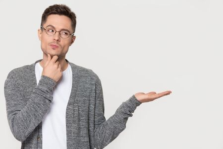 Thoughtful pensive young man in glasses touch chin thinking standing on grey white background isolated studio shot showing empty copy space on open hand palm feels unsure doubtful concept image. Banco de Imagens