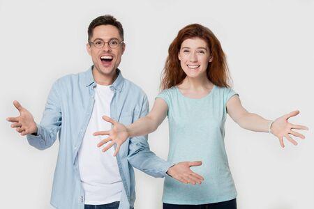 Couple excité heureux souriant fille rousse gars dans des verres regarde la caméra lever les mains faire embrasser le geste de câlin bienvenue ami ou client de salutation agréable de vous rencontrer concept studio image sur mur gris.