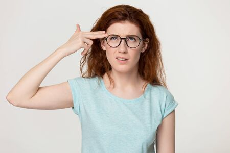 Head shot studio portrait on gray blank wall depressed woman in glasses put fingers to her temple like gun killing herself, tired of someone stupidity, having problems unhappy red-headed girl concept Stockfoto