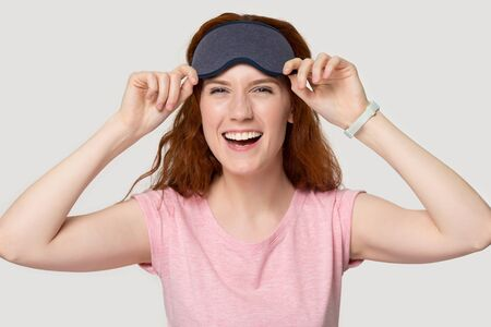 Smiling red-headed woman after sleeping feels well refreshed girl wearing grey eye mask pose isolated on white studio background, comfortable accessory sleepwear, healthy lifestyle enough rest concept Banco de Imagens - 128112745