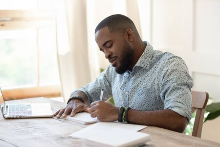 Focused african american man student freelancer making notes studying working with laptop, young black man professional writing essay in notebook preparing for test exam sit at home office desk
