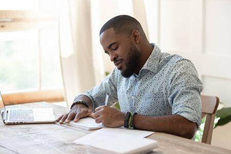 Fokussierter afroamerikanischer Student, Freiberufler, der Notizen zum Arbeiten mit Laptop macht, junger schwarzer Mann, der professionelle Aufsätze im Notizbuch schreibt, die sich auf die Testprüfung vorbereiten, sitzen am Home-Office-Schreibtisch