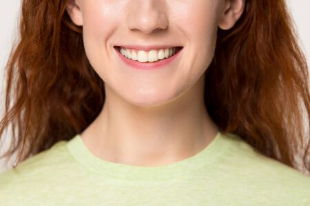 Close up cropped image caucasian attractive red-headed woman with ultra snow white smile healthy straight teeth over grey background. Dentistry dental care, oral health healthcare, whitening concept
