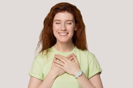 Head shot studio portrait grateful red-headed woman in green t-shirt closed her eyes smiling holds hands on chest pose on grey white background, cupped arms as symbol of sincere feelings appreciation
