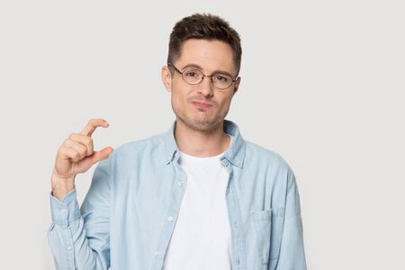 Head shot portrait guy in glasses look at camera showing with fingers something small feels disappointed, man disillusioned about small size length or thickness pose on studio grey wall concept image