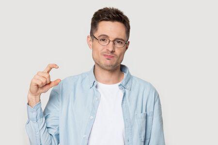 Kopfschuss-Portrait-Typ in Brille schaut in die Kamera, die mit den Fingern etwas Kleines zeigt, fühlt sich enttäuscht, Mann desillusioniert über geringe Länge oder Dicke Pose auf Studio-grauem Wandkonzept