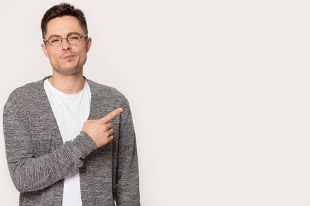 Suspicious millennial man wearing glasses standing over studio gray background looking at camera points finger aside at questionable distrustful announcement, empty copy space ad text concept image
