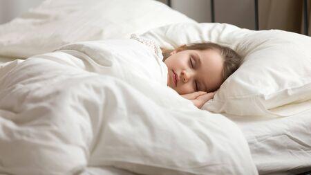 Ruhige entzückende kleine Tochter macht ein Nickerchen. Ruhiges Vorschulkindmädchen bedeckt mit weißer frischer Bettdecke, die im Bett bequeme Matratze im Schlafzimmer liegt. Gesund genug schlafen, zzz, gute Nacht, Konzept