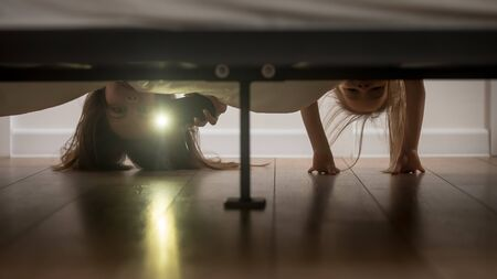 Mother and daughter, babysitter and kid girl afraid of monsters hold smartphone shine a flashlight under the bed looking on floor check ghosts, older younger sisters playing having fun at home concept
