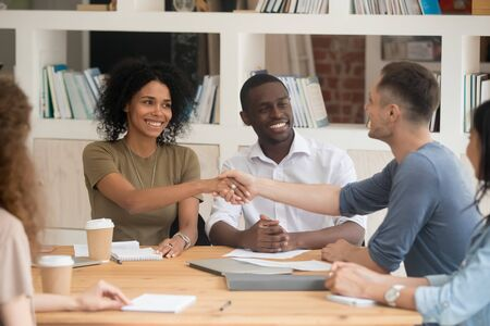 African caucasian man woman shaking hands at company meeting in office boardroom, gesture of greeting or getting acquainted, diverse colleagues sitting at table starting business negotiations concept