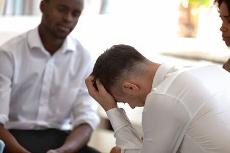 Rear side view fired employee feels desperate sitting with diverse colleagues. People at group therapy listen story of guy sympathize with him, share personal problems addictions traumas rehab concept