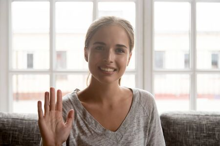 Happy woman sit on sofa at home waving hand to camera head shot, girl makes video call informal conversation with friends talk online to relatives, greet employer during internet job interview concept Stock Photo