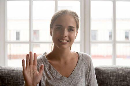 La donna felice si siede sul divano a casa agitando la mano alla telecamera, la ragazza fa una videochiamata conversazione informale con gli amici parla online con i parenti, saluta il datore di lavoro durante il concetto di colloquio di lavoro su Internet Archivio Fotografico