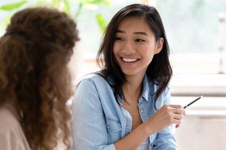 Étudiante asiatique regardant un camarade de groupe parler étudier apprendre se préparer à l'examen assis dans la salle de classe, divers amis employés travaillant ensemble sur un nouveau projet communiquant discuter de l'image conceptuelle Banque d'images