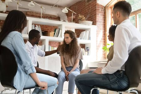 Diverse people sit in circle together at group therapy discuss share personal problems, african psychologist supporting encouraging newcomer shy girl. Medical detox center, psychological help concept Stock Photo