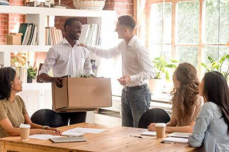 Company boss and staff millennial members gathered in office greeting newcomer african man employee, new worker holds carton box with personal belongings starting career in company feels proud happy Stock Photo