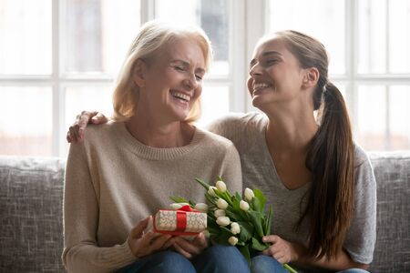 Overjoyed beautiful middle aged mother sit with grown up daughter hold gift and flowers family laughing celebrating life event, birthday or spring holiday 8-march International Women Day feeling happy 版權商用圖片 - 128089188